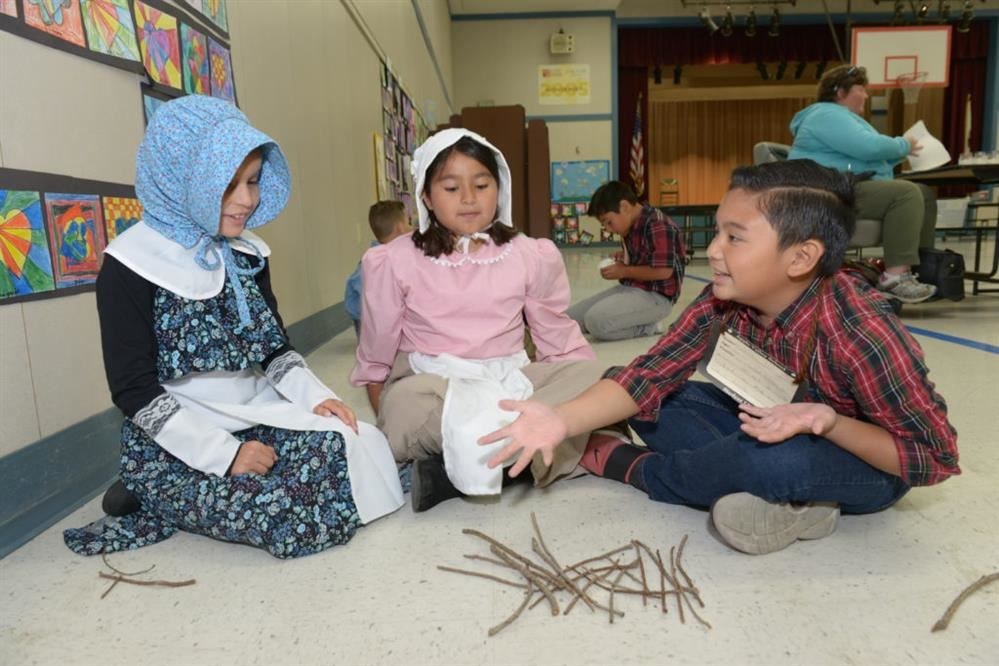 Students dressed in pioneer clothing playing a pioneer game