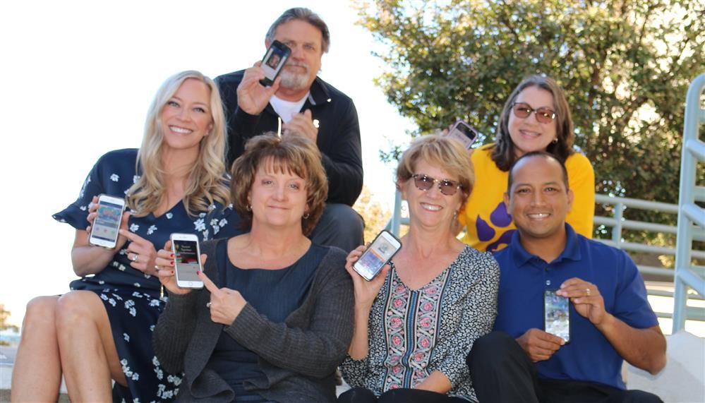 Principals holding phones with app